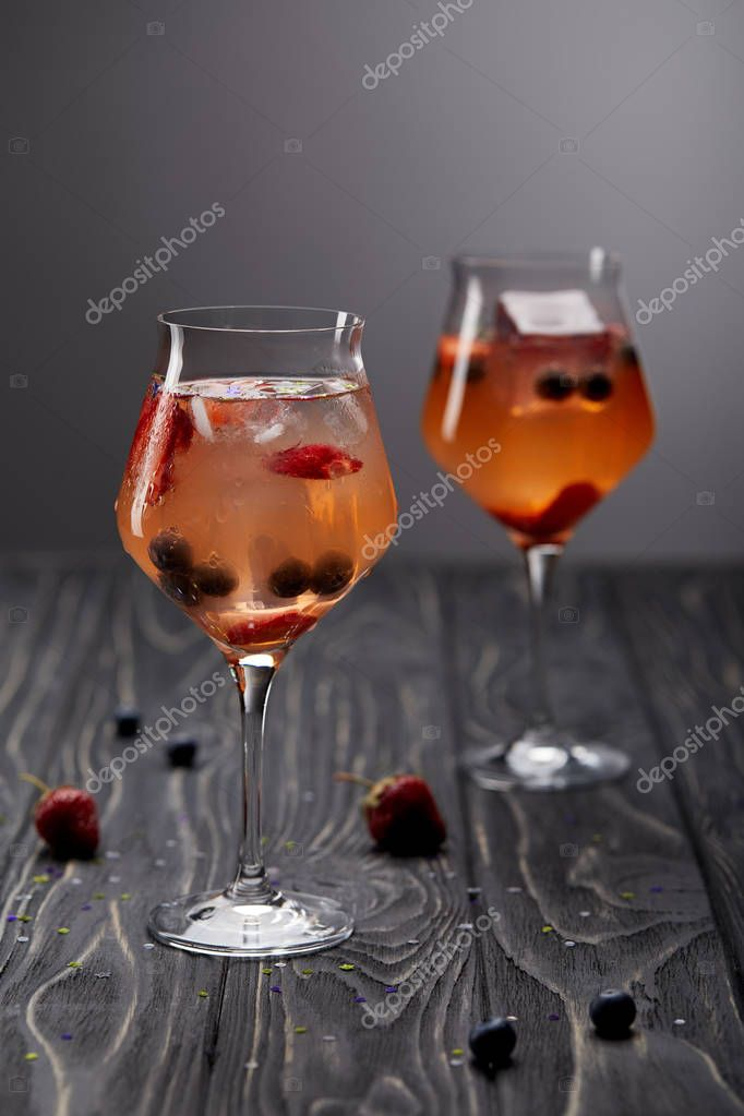 Two glasses of lemonade with ice cubes, strawberries and blueberries on grey background stock vector