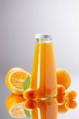 Photo bottle of fresh orange juice with oranges and kumquats on reflective surface