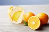 Fotografie sklenice osvěžující limonádu s zralé pomeranče na dřevěný stůl