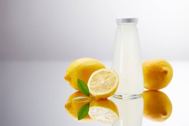 glass bottle of delicious lemonade with lemons on reflective surface and on grey