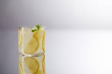 Single glass of fresh lemonade on reflective surface and on grey stock vector
