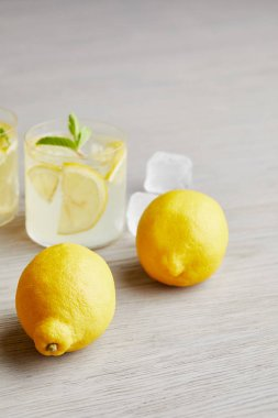 lemonade with ripe lemons on wooden surface