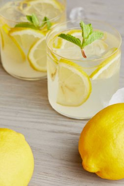close-up shot of glasses of lemonade with ripe lemons on wooden surface