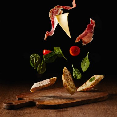 Fresh salad with jamon and cheese for sandwich falling on wooden cutting board