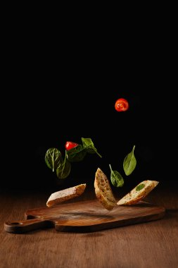 Bread pieces and salad leaves with tomatoes flying above wooden table surface
