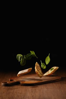 Bread pieces and salad leaves flying above wooden cutting board