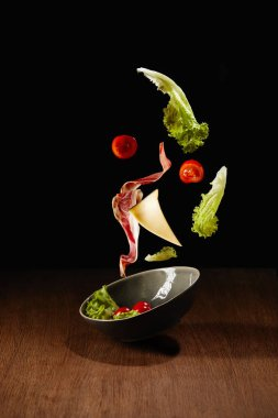 Fresh salad with meat and cheese falling in bowl above wooden table surface
