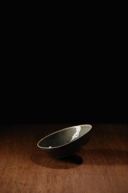 Empty ceramic bowl flying above wooden table surface