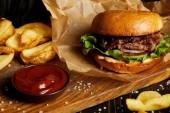 Hamburger a hranolky podávané na dřevěném prkénku s omáčkou