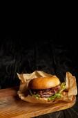 Lákavé rychlé občerstvení restaurace s hamburger na dřevěné desce