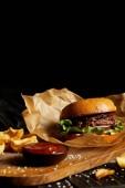 Hamburger a hranolky se solí a omáčkou na dřevěné desce