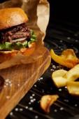 Lákavé rychlé občerstvení Restaurace Zlatý hranolky a hamburger na dřevěný stůl