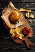 Pohled shora sady foodu burger s brambory, podávané na dřevěném prkénku