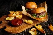 Lákavé rychlé občerstvení restaurace s hamburgery a brambory s omáčkou na prkénku