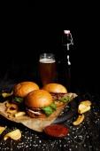 Verlockend, Fast-Food-Hamburger und Pommes frites auf Tisch mit Bier in der Flasche und Glas