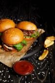 Verlockend Fast-Food-Diner mit Hamburgern und Kartoffeln auf Holztisch