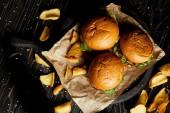 Draufsicht auf Hamburger und Pommes auf Bastelpapier
