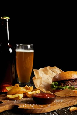 Hamburger and french fries served with cold beer on wooden board