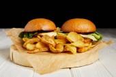 Hamburger und Pommes auf Bastelpapier auf weißem Tisch serviert