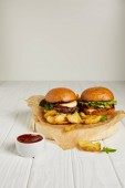 verführerisches Fast-Food-Diner mit Hamburgern und goldenen Kartoffeln serviert mit Sauce auf dem Tisch