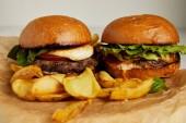 Fotografie Junk food koncept s hamburgery a smažené brambory na kraftový papír