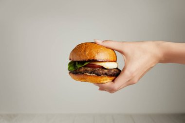 Hot tasty burger in female hand on grey background