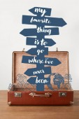 Fotografia Open vintage suitcase with arrows and lettering - My favorite thing is to go where I have never been