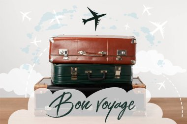Stacked old leather travel bags with airplanes and Bon voyage (have a nice trip) inspiration