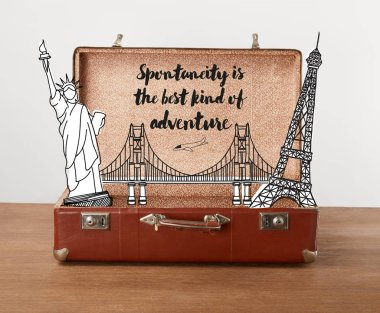 Open vintage travel bag with illustration and lettering - Spontaneity is the best kind of adventure