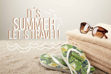 close up view of stack of towels, sunglasses and summer flip flops on sand on grey backdrop with