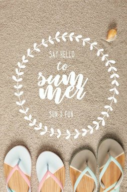 flat lay with summer flip flops and seashell on sand with