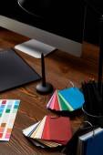 Detailní zobrazení grafického návrháře pracoviště s barevné palety, grafický tablet a obrazovku počítače na dřevěný povrch