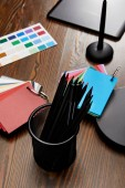 Fotografie close up view of graphic designer workplace with colorful pallet and graphic tablet on wooden surface