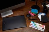 Detailní zobrazení grafického návrháře pracoviště s barevné palety, obrazovku počítače a grafický tablet na dřevěný povrch