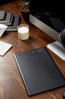 close up view of graphic designer workplace with graphic tablet, glass of milk and notebooks on wooden tabletop