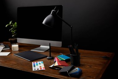 close up view of graphic designer workplace with colorful pallet, graphic tablet, computer screen and lamp on wooden surface