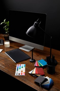 Close up view of graphic designer workplace with colorful pallet, graphic tablet, blank computer screen and lamp on wooden surface stock vector