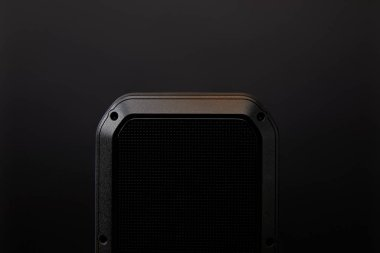 close up view of black audio speaker on black wall backdrop