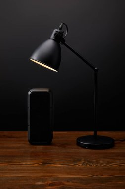 close up view of black audio speaker and lamp on wooden surface on black wall backdrop