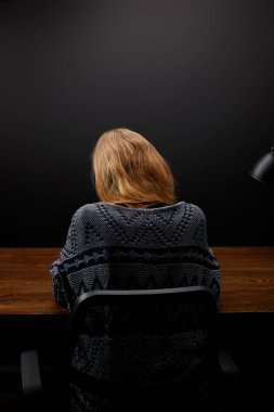 back view of woman sitting at wooden tabletop with black wall backdrop
