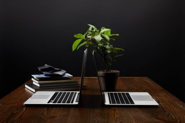 close up view of designer workplace with laptops, notebooks and pallet on wooden tabletop on black wall backdrop