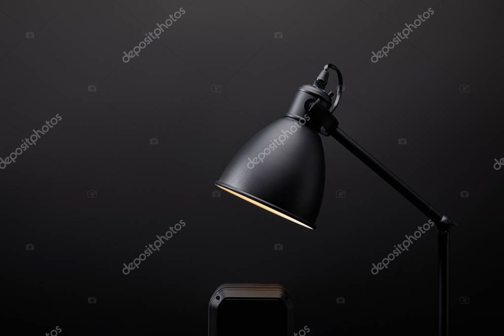 close up view of black audio speaker and lamp on black wall backdrop