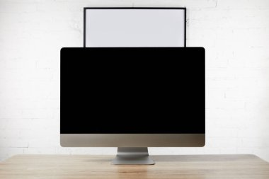 close up view of designer workplace with blank computer screen on wooden surface and empty white board on brick wall