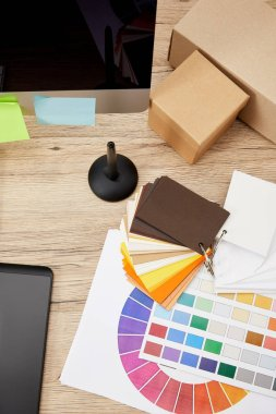 Top view of graphic designer workplace with arranged computer screen, colorful stickers, graphic tablet and pallet on wooden surface stock vector