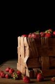 Fotografie freshly harvested strawberries in rustic box on black