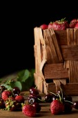 ripe cherries and strawberries on wooden surface with leaves and rustic box on black