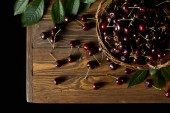 top view of fresh ripe cherries in old basket on wooden table isolated on black