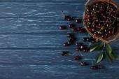 Fotografie top view of ripe cherries in basket on blue wooden surface