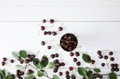 top view of fresh ripe cherries in cup on white wooden tabletop with leaves branch