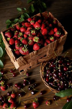 high angle view of cherries and strawberries in basket and box on wooden surface